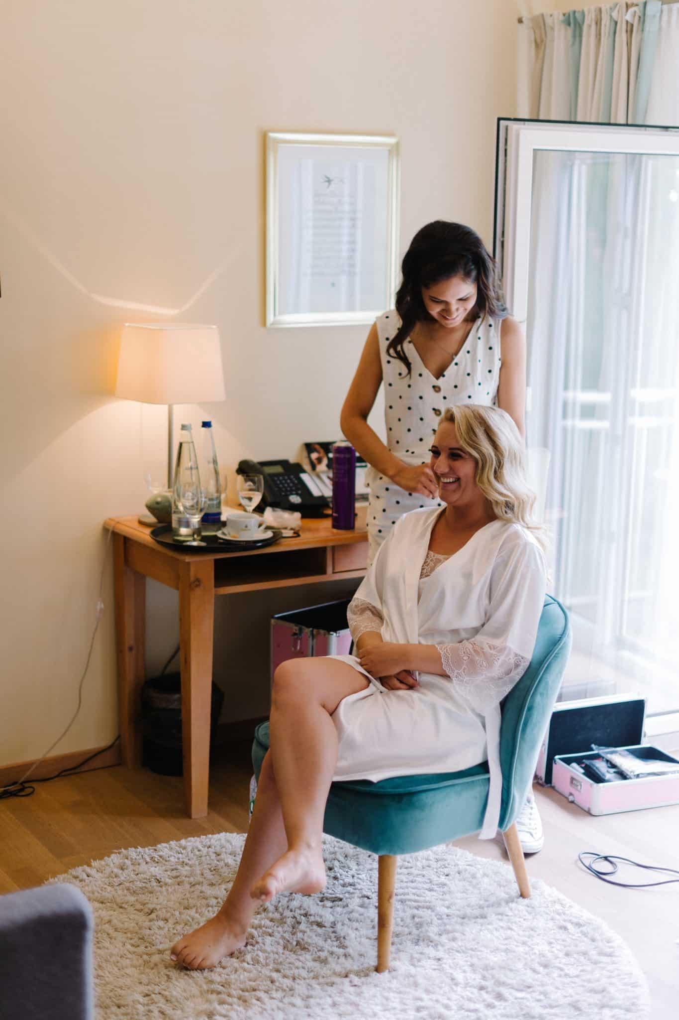 Eine Braut beim Getting Ready. Sie sitzt und ihre Haare werden gerade gestylt.