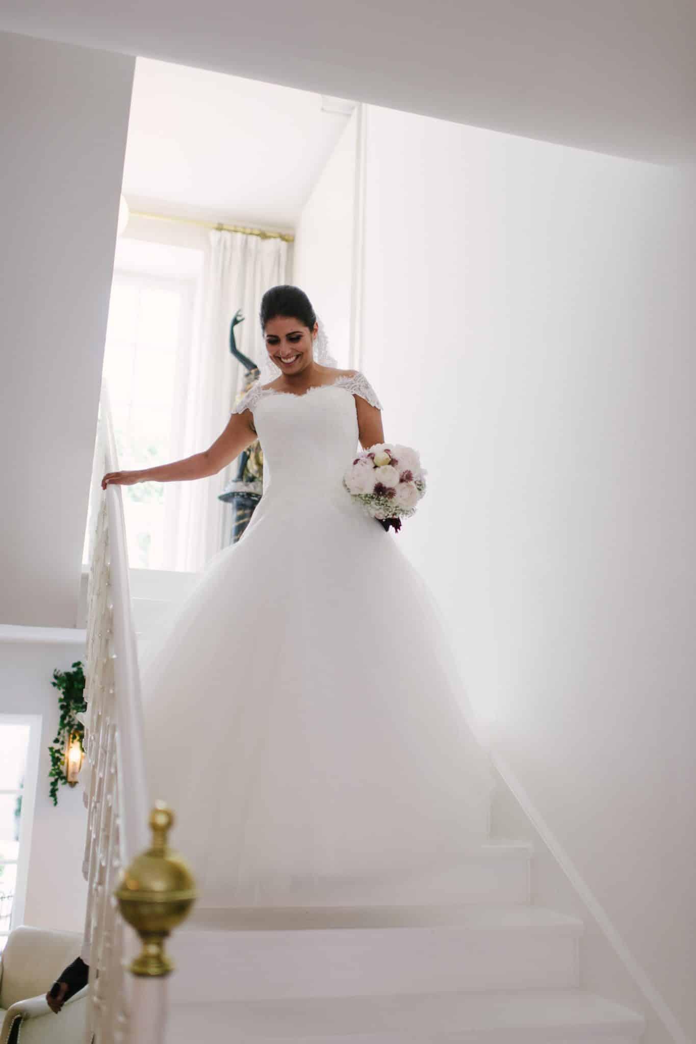 Die Braut geht gerade die Treppen herunter.
