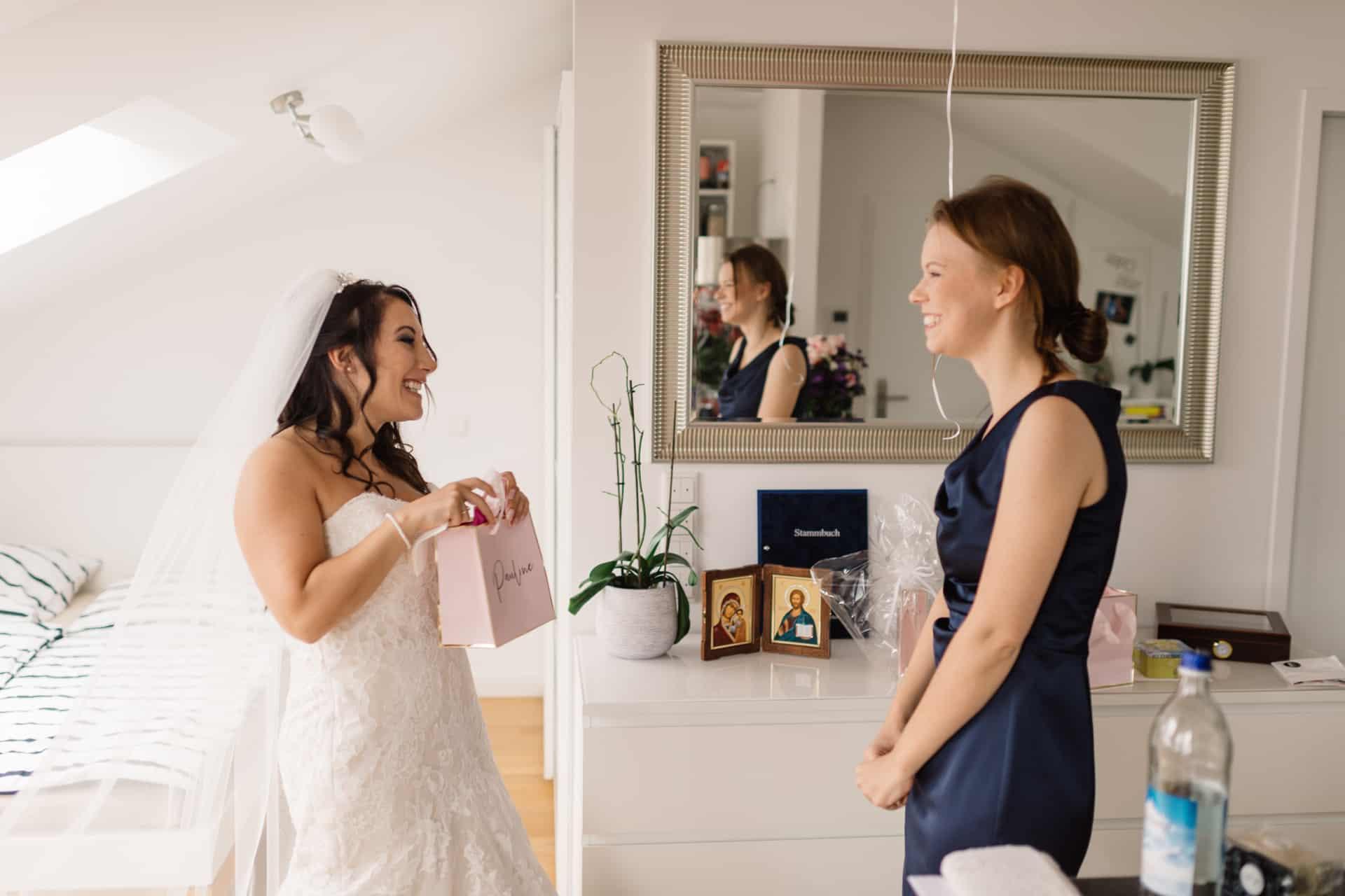 Die Braut schenkt der Brautjungfer ein Geschenk.